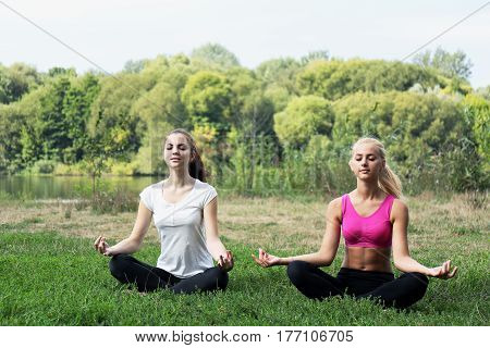 Two young women doing yoga on the river bank