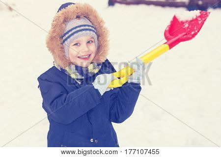 A child is playing with snow with a shovel in the winter. The boy smiles and throws snow by typing it into the children's shovel.