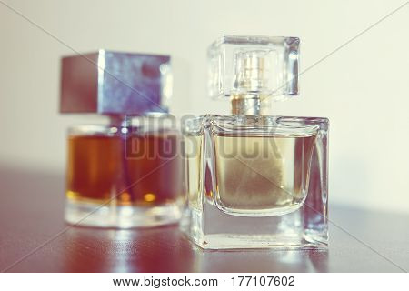 Two bottles of perfume on the table. Delicious smell, fragrance, elegant bottles of perfume. The perfume on the table.