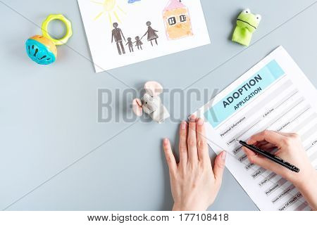 adoption form with hands in family concept on gray background top view mock-up