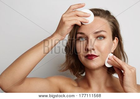 Young woman takes off white makeup sponge, looking at the camera