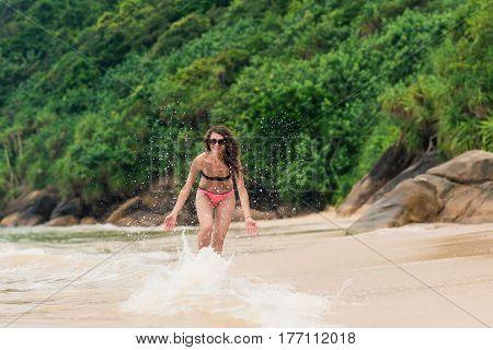 Beach vacation. Hot beautiful woman in bikini having fun on a big waves in ocean.