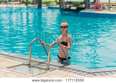 Portrait of a beautiful woman getting out of a swimming pool in hotel resort. Asia