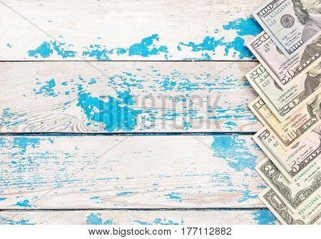 Different US dollar bills on wooden background.