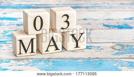 May 3rd. Wooden cubes with date of 3 May on old blue wooden background.