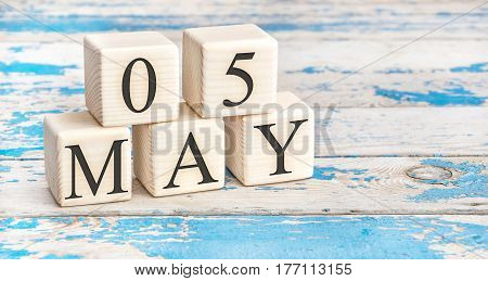 May 5th. Wooden cubes with date of 5 May on old blue wooden background.