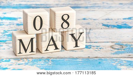 May 8th. Wooden cubes with date of 8 May on old blue wooden background.