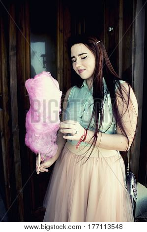 Pretty Young Woman With Dark Long Hair And Blue Eyes Walking On The Harbour, Hold Pink Candy Cotton