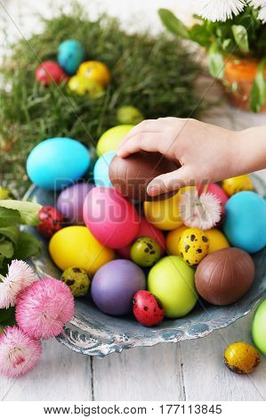Multicolored eggs with flowers. Easter conceptual background. The child takes an egg