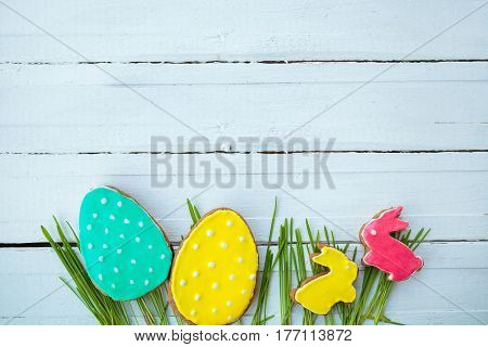Happy easter. Easter background. Easter cookies. Gingerbread in the form of colored Easter rabbits and eggs on green grass on a background of white wooden desk. Free space