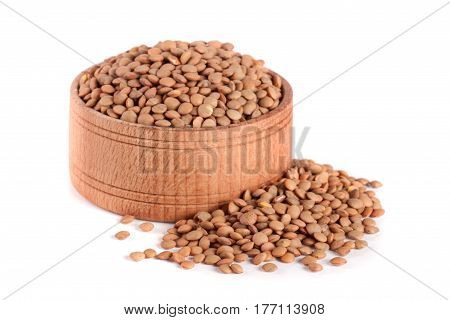 Lentils in a wooden bowl isolated on a white background.