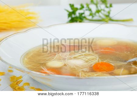 Chicken soup with noodles and vegetables in white plate