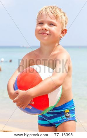 Cute funny happy little boy playing in the water waves at sea ocean on a sunny day