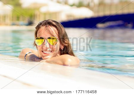 Young hispanic woman relaxing in pool on summer vacations
