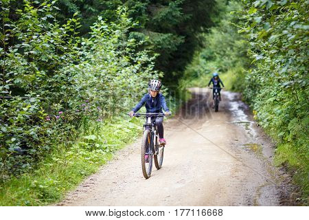 Teenage girl in helmet riding the bicycle on mountain road