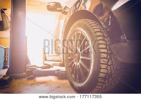 Car in garage of auto repair service shop with special repairing equipment with sun light effect filter