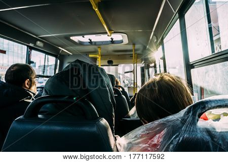 Interior of the bus from the rear seat, passengers in the sun, perspective