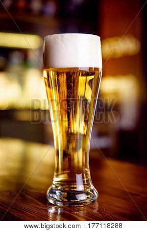 A glass of lager placed on the pub counter. Horizontal indoors shot.