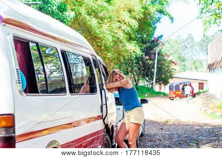 Beautiful young girl with blond hair is standing leaning on a minibus window