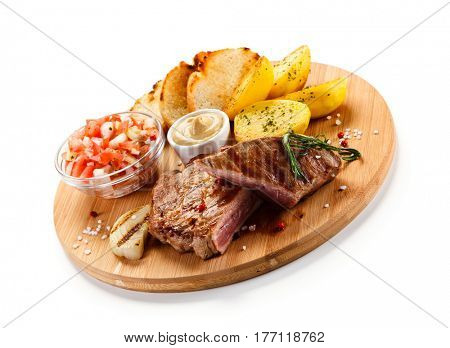 Steaks, baked potatoes and vegetable salad