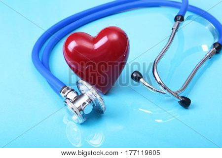 Medical stethoscope and red heart isolated on blue mirror background.
