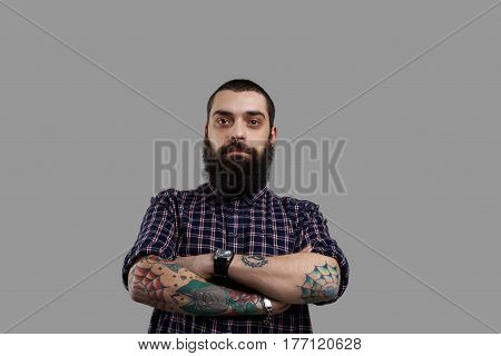 Isolated brutal bearded man with tattooed hands on grey background. Football fun look to the camera. Guy drink a lof of beer and have big stomach. Serious emotion on the face of aggressive person.