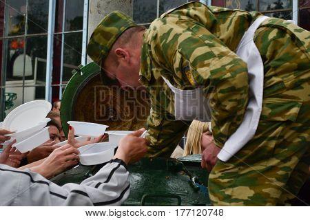 PYATIGORSK RUSSIA - MAY 09 2011: military man distributes food of hungry people