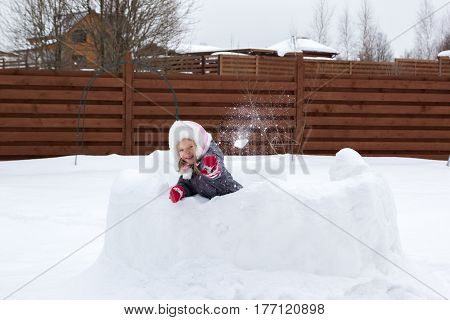 Girl In Snow Fortress Playing Snowballs