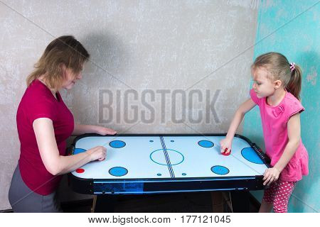 Mom And Daughter Playing Air Hockey