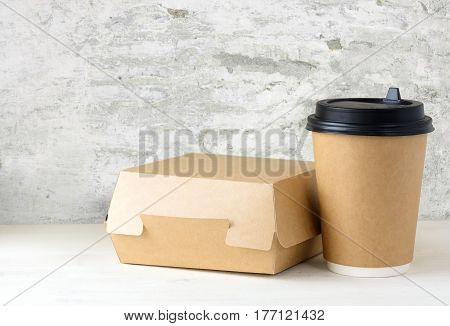 craft paper coffee cup and food box on the white table near the white wall with damaged plaster
