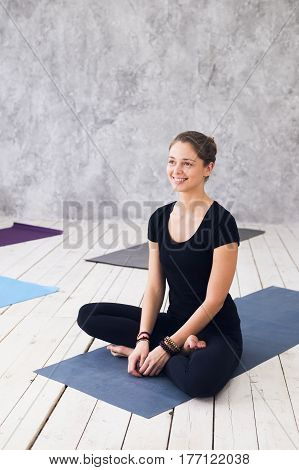 Young attractive woman practicing yoga, sitting in Ardha Padmasana exercise, Half Lotus pose, working out, wearing black t-shirt, pants, meditation session at floor at yoga class.
