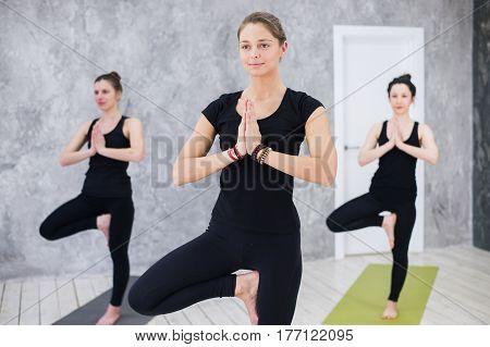 Smiling yogi girl in class in Yoga asana, exercising, stretching.