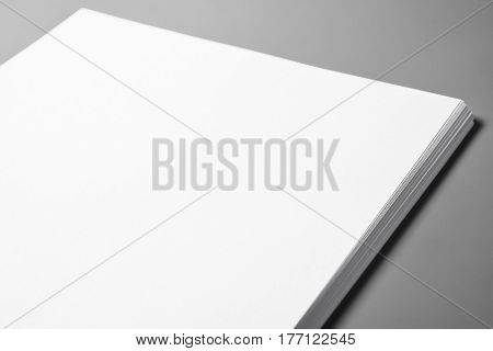 Pile of blank sheets of paper over grey background