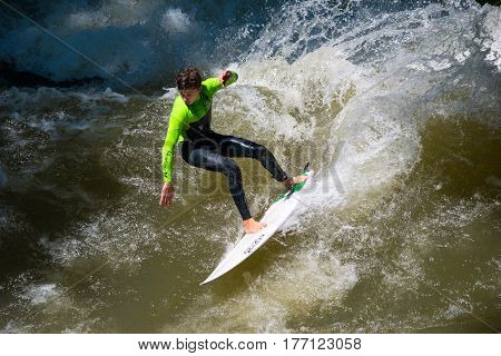 Munich, Germany - June 7, 2016: Boarders surfing on the Isar river in Munich, Bayern, Germany