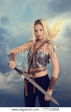 female warrior with sword and hair blowing in wind