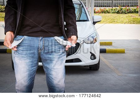 Man showing his empty pockets with white car on the car park.