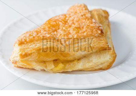 Apple turnover pastry on plate with white background close up