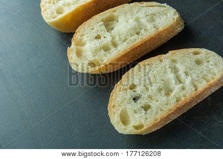 Three sliced baguette pieces on black surface angled view