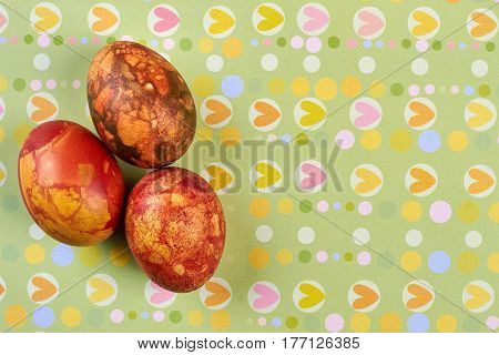 Eggs on heart pattern background. Colored Easter eggs, top view. God is love.