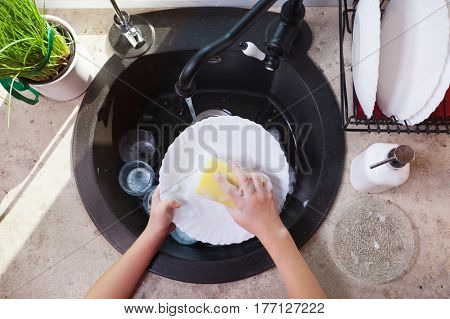 Child hands scrubbing a plate with sponge in the kitchen sink - top view of washing up