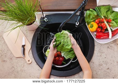 Child hands washing vegetables at the kitchen sink - top view with lettuce leaf under the tap