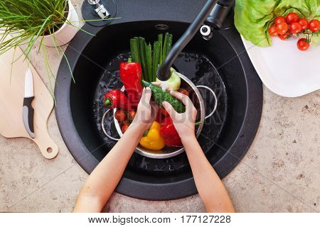 Child hands washing vegetables at the kitchen sink - top view with a cucumber under the tap and other salad ingredients