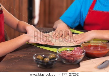Kids preparing a pizza - stretching the dough in the baking pan, closeup on hands, shallow depth