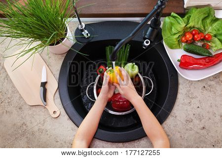 Child hands washing vegetables at the kitchen sink - top view with a bellpepper under the tap and other salad ingredients