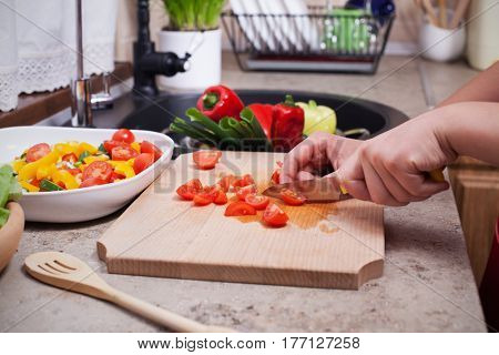 Closeup on child hands slicing cherry tomatoes for a fresh vegetables salad - with the ingredients around