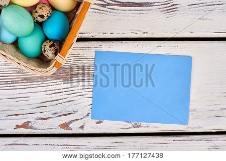 Easter basket with empty card. Paper on white wooden background. Send Easter letter to friend.