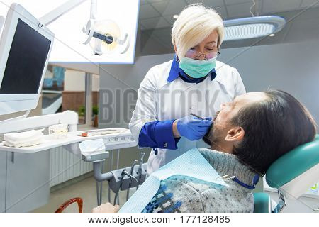 Dentist lady working with patient. Examination at dentist office. Medicine and healthcare.