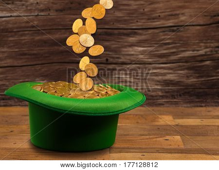 Treasure of pure gold coins pouring down onto a green velvet hat on wooden table. Concept image to celebrate luck on St Patrick's Day of March 17th