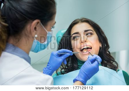 Young woman at the dentist. Stomatologist holding concave mirror. Check your teeth.