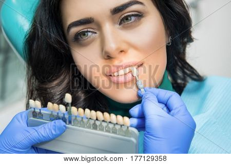 Dentist holding tooth color chart. Face of a young female.